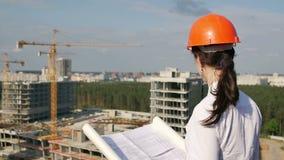Kvinnaarkitekten kontrollerar konstruktionsplatsen stock video