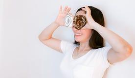 Kvinnaasia b?rande vita skjortor som rymmer donuts royaltyfria foton