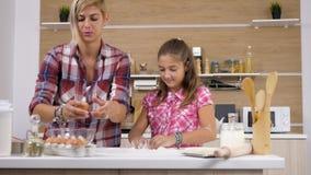 Kvinnaavbrott ett ägg, medan hennes dotter spelar med mjölet stock video