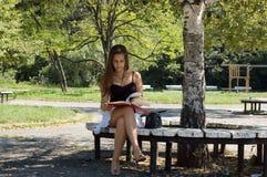 Kvinnaavläsningsbok i park arkivfoton
