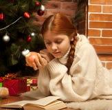 Kvinnaavläsningsbok på jul framme av treen Royaltyfria Foton