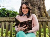 Kvinnaavläsningsbok på parkbänk Arkivfoto