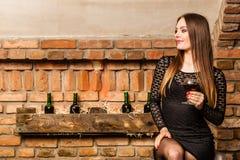 Kvinnaavsmakningvin i lantlig stugainre Royaltyfri Foto