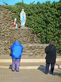 Kvinnaböner framme av en Lourdes grotta, katolsk relikskrin Fotografering för Bildbyråer