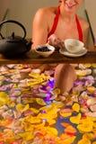 Kvinnabadning i brunnsort med färgterapi Arkivbild