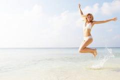 Kvinnabanhoppning i luften på den tropiska stranden Fotografering för Bildbyråer
