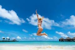 Kvinnabanhoppning i luften på den tropiska stranden arkivfoto