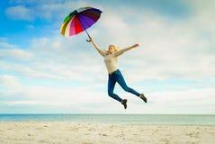 Kvinnabanhoppning med det färgrika paraplyet på stranden Arkivbilder