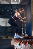 Kvinnabanhoppning på gummihjulet i den CrossFit idrottshallen Arkivfoto