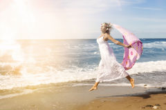 Kvinnabanhoppning på stranden med sjalen i vinden Fotografering för Bildbyråer