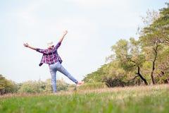 Kvinnabanhoppningen som tycker om, kopplar av på grönt gräs och blommafält in Arkivbild