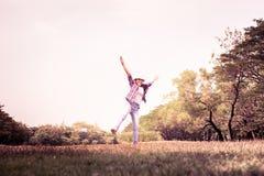 Kvinnabanhoppningen som tycker om, kopplar av på grönt gräs och blommafält in Arkivfoton