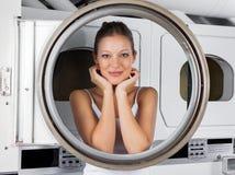 Kvinnabenägenhet på dörr för tvagningmaskin arkivfoton