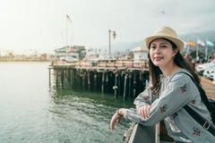 Kvinnabenägenhet på ledstången på hamnplatsen arkivfoto