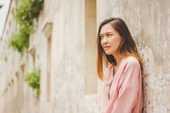 Kvinnabenägenheten mot den gamla cementväggen royaltyfri fotografi