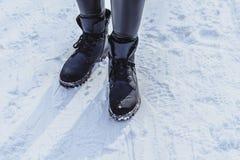 Kvinnaben i kängor på snön royaltyfri foto