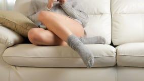 Kvinnaben kopplade av att sitta på en soffa lager videofilmer