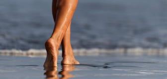 Kvinnaben och fot som g?r p? sanden av stranden arkivfoton