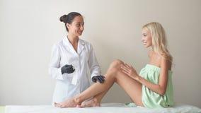 Kvinnaben och hårborttagning med smärtsamt tillvägagångssätt för varmt vax Kvinna i en skönhetsalong som gör depilation Vaxdepila lager videofilmer
