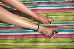 Kvinnaben på den randiga handduken arkivfoto