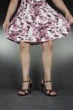 Kvinnaben som bär svarta häl och klänningen Royaltyfri Bild