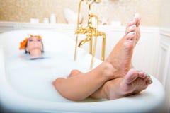 Kvinnaben som ligger i det vita badkaret royaltyfri foto