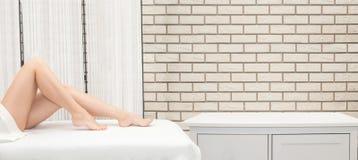 Kvinnaben som sitter på för hårborttagning för soffa ett hemmastatt begrepp royaltyfri foto