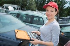 Kvinnabilmechanicianen reparerar motorbilen och ler Royaltyfri Fotografi