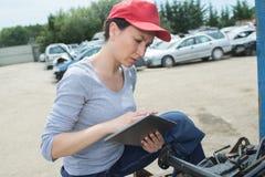Kvinnabilmechanicianen reparerar motorbilen utomhus Royaltyfri Fotografi