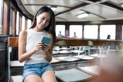 Kvinnablick på mobiltelefonen och tafärjan i Hong Kong royaltyfri foto