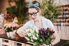Kvinnablomsterhandlare som tar omsorg av tulpan i blomsterhandel Arkivfoto