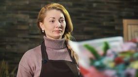 Kvinnablomsterhandlaren, ger en bukett av blommor till kunden arkivfilmer