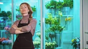 Kvinnablomsterhandlaren ser kameran, på bakgrunden av ställer ut av blommor stock video