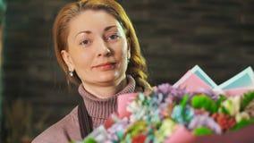 Kvinnablomsterhandlaren visar en härlig bukett av blommor close upp stock video