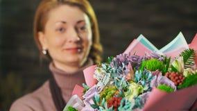 Kvinnablomsterhandlaren visar en härlig bukett av blommor close upp lager videofilmer