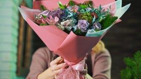Kvinnablomsterhandlaren visar en härlig bukett av blommor close upp arkivfilmer