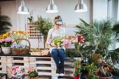 Kvinnablomsterhandlaresammanträde och ordna rosa tulpan i blomsterhandel Fotografering för Bildbyråer