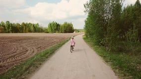 Kvinnabonden i klänning rider en cykel på vägen stock video
