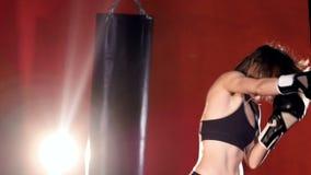 Kvinnaboxning med att stansa påsar långsam rörelse arkivfilmer