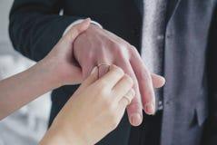 Kvinnabruden sätter den guld- cirkeln på fingret av brudgummen, frankt monent av bröllopdagen arkivfoto