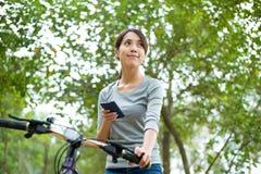 Kvinnabruk av den smarta telefonen och att rida en cykel Royaltyfri Foto