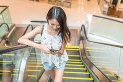 Kvinnabruk av mobiltelefonen på rulltrappan i shoppinggalleria Arkivfoton