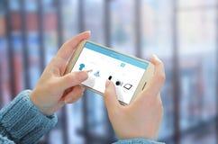 Kvinnabruksmobiltelefon som köper kläder och tech Exponeringsglas av affärsmitten i bakgrund Arkivbild