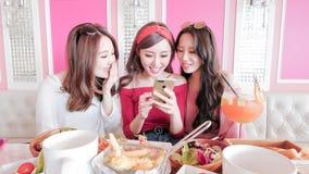 Kvinnabrukstelefon i restaurang arkivbild