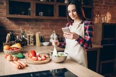 Kvinnabrukstelefon, medan laga mat grönsaksallad royaltyfria bilder