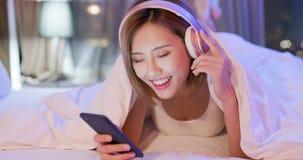 Kvinnabrukstelefon som lyssnar musik arkivbild