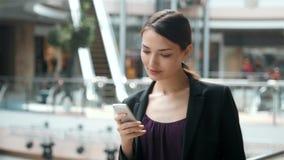 Kvinnabrunett med telefonen som tätt ler upp ståenden Lycklig ung professionell för affärskvinna Härligt multietniskt stock video