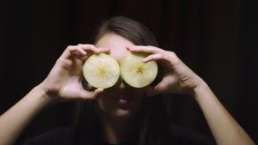 Kvinnabrunettflicka som rymmer en äpplefrukt på deras ögon mot en mörk bakgrund Sunt banta, banta, syna det vård- begreppet stock video