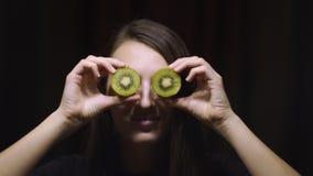 Kvinnabrunettflicka som rymmer en kiwi på deras ögon mot en mörk bakgrund lager videofilmer