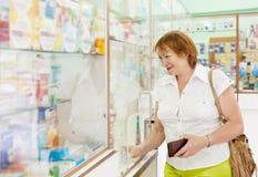Kvinnabuysdroger på apoteket royaltyfri foto